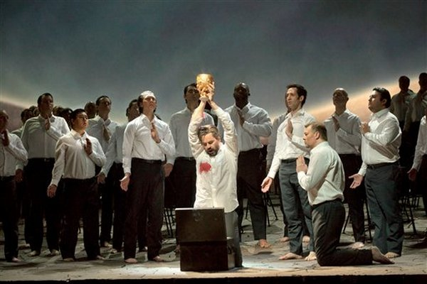 White-shirted knights venerate the Grail, as Amfortas (Peter Mattei) holds it aloft. Gurnemanz (René Pape) kneels. Phot Ken Howard/Metropolitan Opera.
