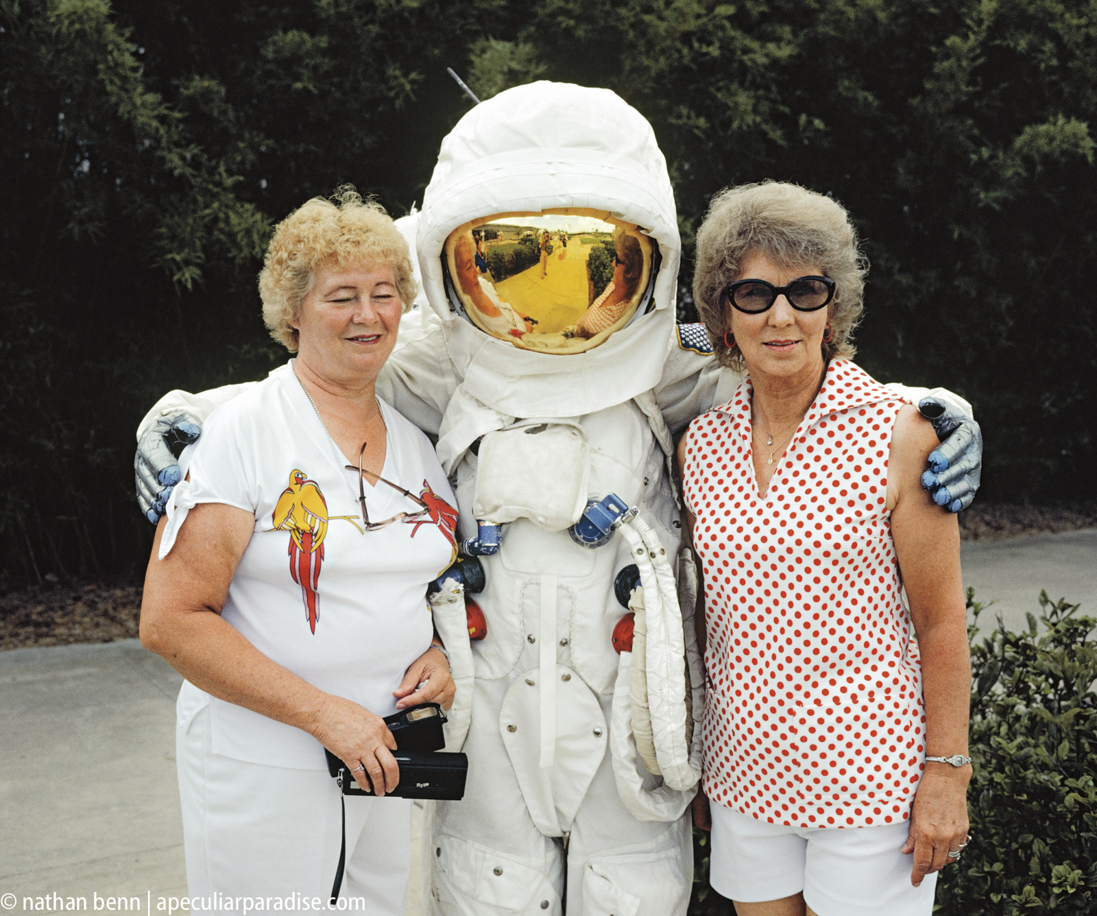 Tourists to the Kennedy Space Center in Orlando, Florida posing with a pretend astronaut in an Apollo spacesuit. Administered by N